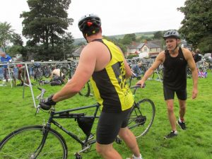 At transition with bike - guide in bright yellow looking back to VI who has hand on saddle