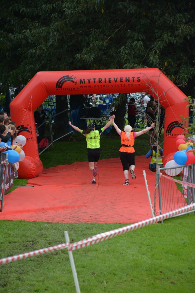 VI and Guide with their arms aloft as they run through the inflatable orange finishing arch