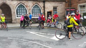 Large group of brightly coloured tandem cyclists about to set off after a cafe stop