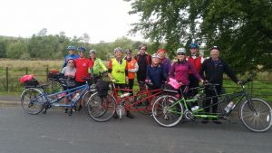 A group of 12 cyclists and bikes posing for a group photoshot