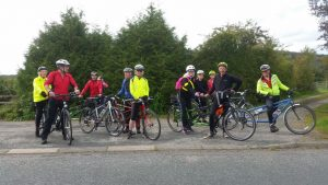 Team of brightly coloured tandem cyclists and instructors stationary just off of the road