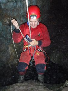 VI abseiling down a caving shaft using a petzyl descender
