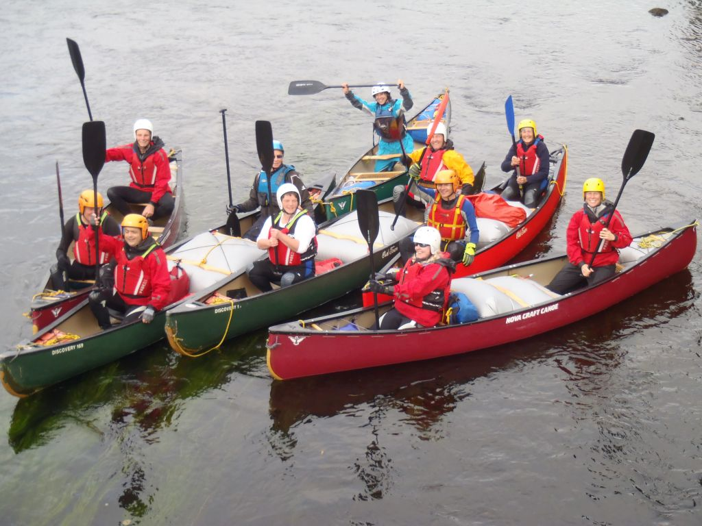 end of trip celebratory picture with 6 canoes rafted together, canoeists with raised paddles