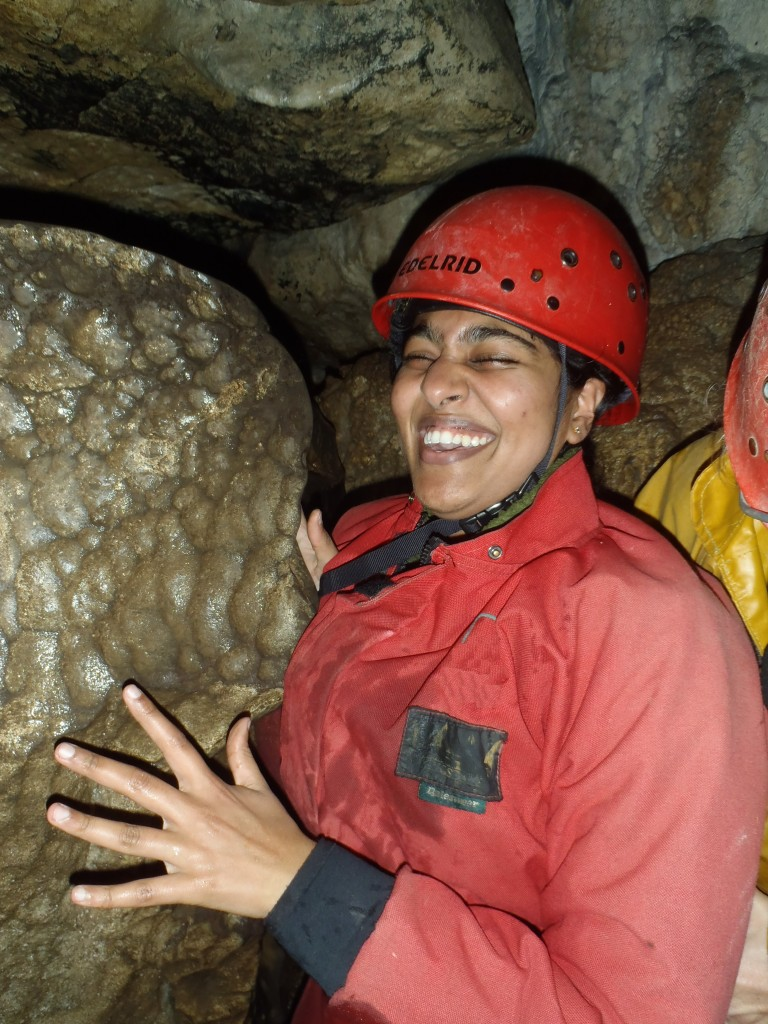 Happy smiling caver getting to grips with some rock