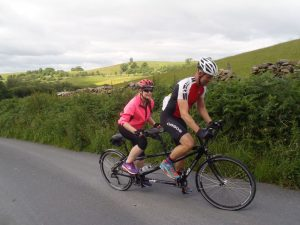 Pilot and Stoker both standing on the pedals whilst cycling up a hill in the Dales