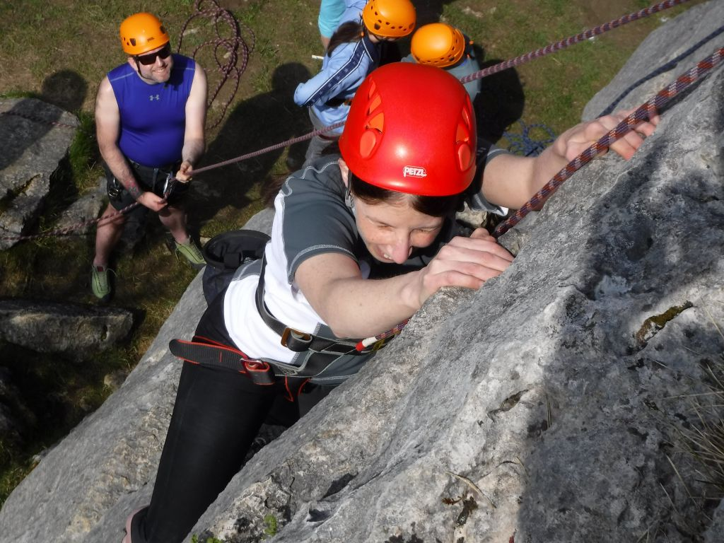 VI in close proximity to the rock with hands in pocket holds above with her belayer coaching her