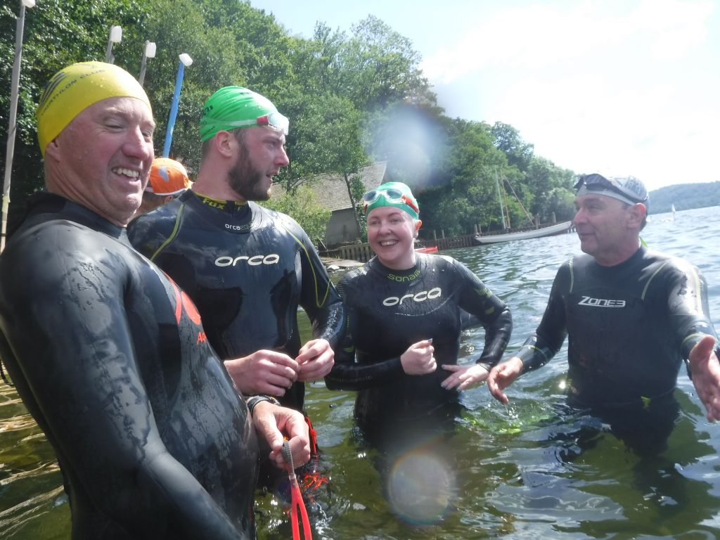 4 wet suited swimmers standing in the water sharing a joke together