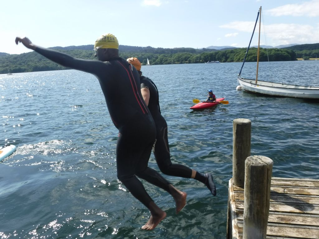 VI and guide wearing wetsuits leaping into the water off of a wooden jetty in Lake Windermere.
