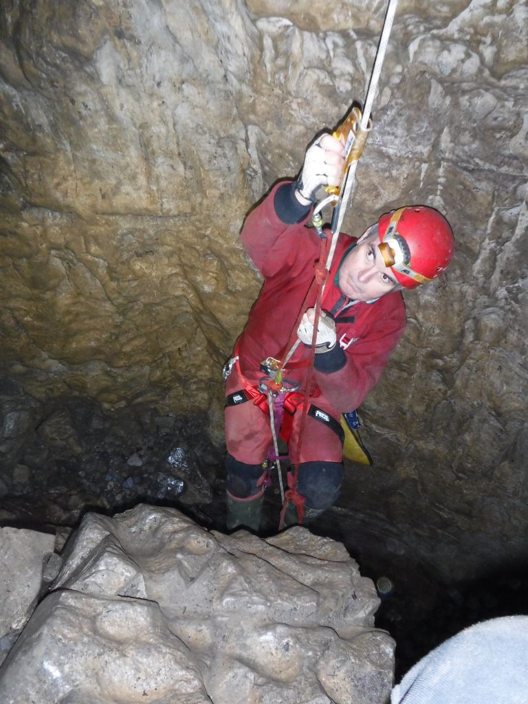 Caver using hand and foot jammers to ascend a rope.