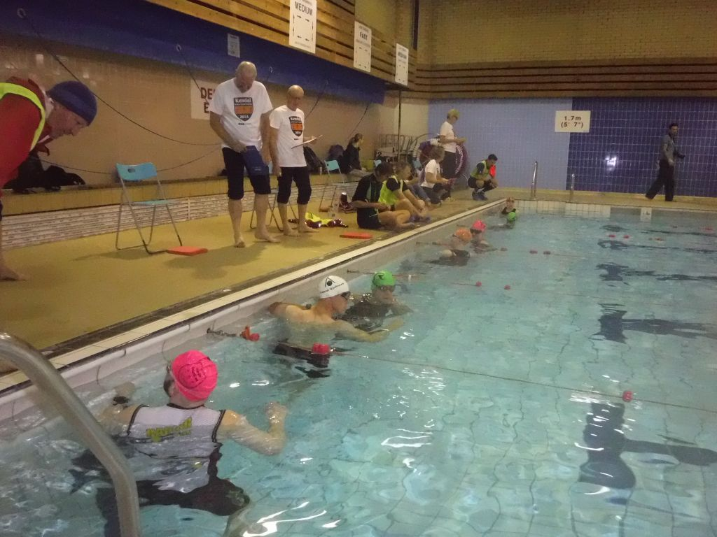 At the swimming pool start of a triathlon. Athlete and guides in the water, Lane counters and coaches on the poolside.