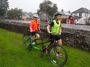 female VI and guide running with their tandem in transition at the start of cycling leg.
