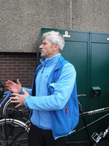 Triathlon coach standing in front of bikes gesticulating with hands after an event