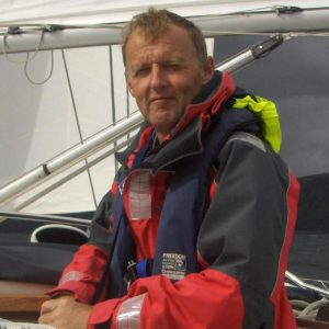 Dave C sitting on the coach roof of a yacht