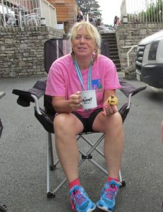 Founder Jill Corso sitting in a camping chair eating cake at the end of a triathlon event