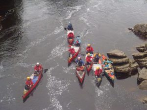 Ariel shot of 7 canoes rafted together next to some big flaked rocks