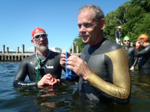 Two triathletes in standing chest deep in water