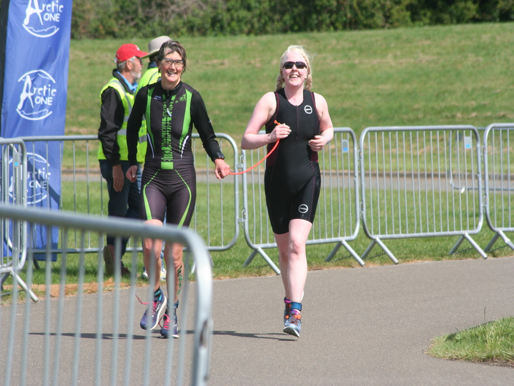 Andrea and kath smiling as they approach the finishing line