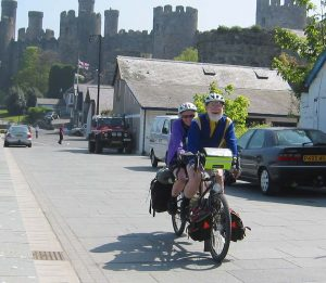 Matt and Mary cycling in sunny Conwy with the Castle in the background