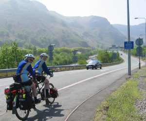 Matt and Mary cycling the wrong way on the slip road near Conwy in Wales
