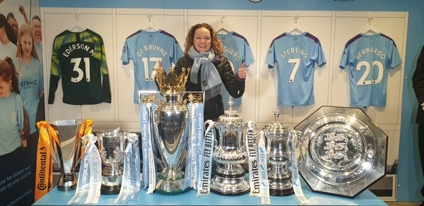 Lucy hiding behind the many trophys won at Manchesgter City